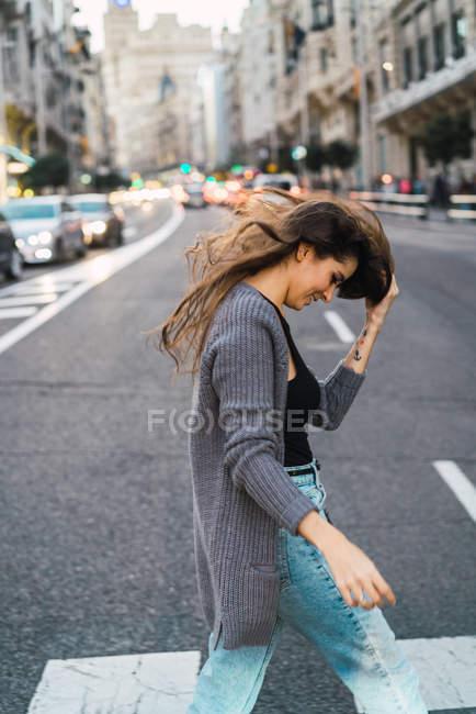 Side view of brunette girl waving hair street scene — Stock Photo