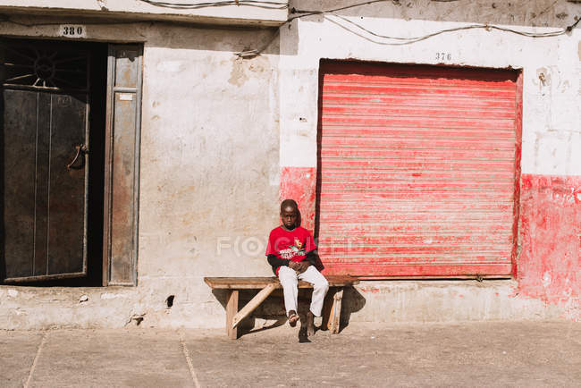 Goree, Senegal- December 6, 2017: Barefoot African kid sitting on bench on paved street in bright light. — Stock Photo