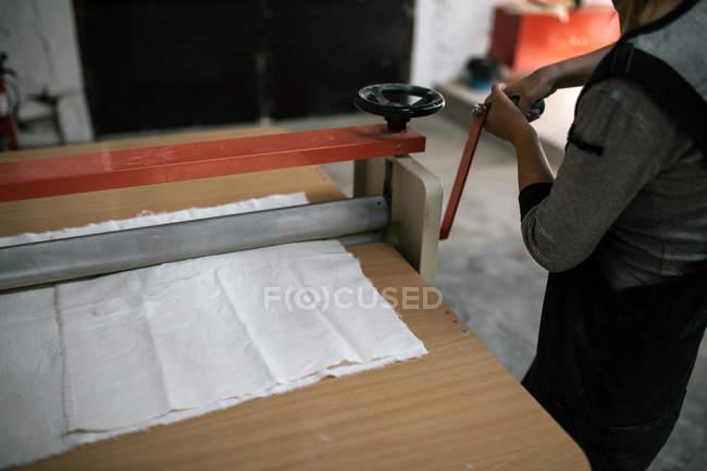 Crop image of artisan adjusting machine on table at workshop — Stock Photo