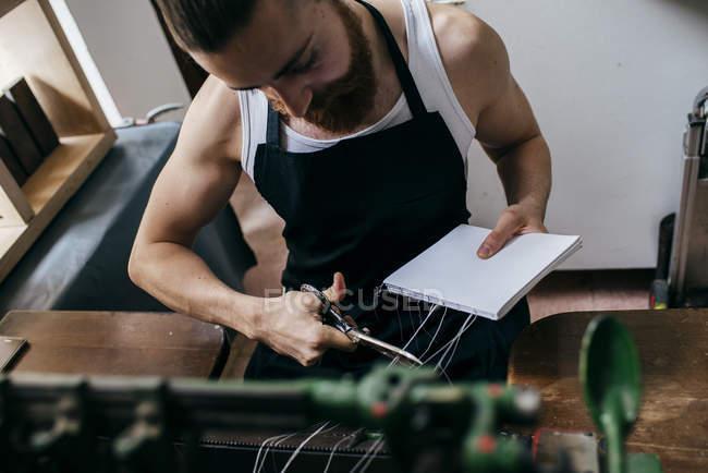 Портрет бородатого мастера в типографии переплетных книг . — стоковое фото
