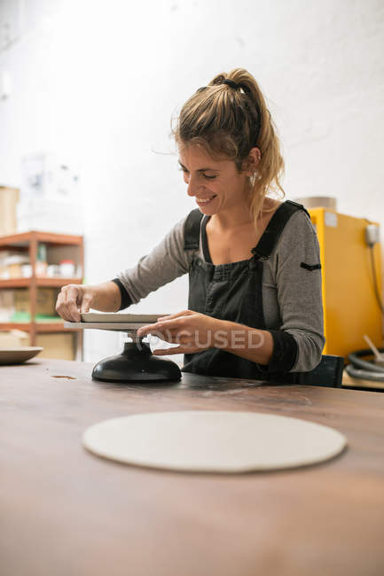 Portrait of blonde woman working with clay at desk — Stock Photo