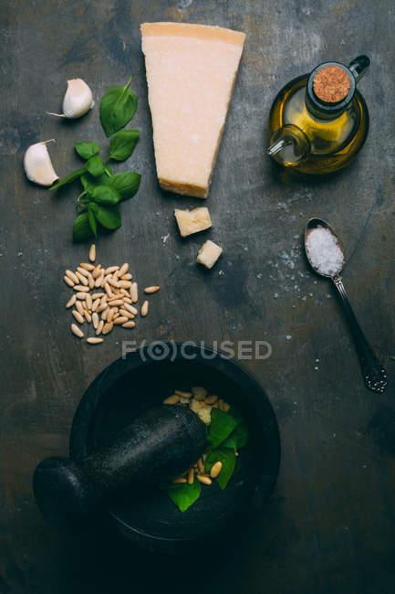 Непосредственно над видом песто соус ингредиентов на темной таблицы — стоковое фото