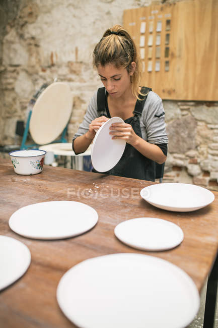 Concentrated potter sitting at table and forming plates from white clay. — Stock Photo