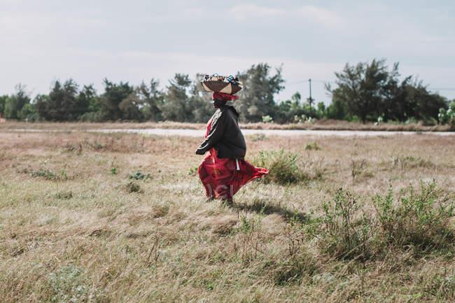 Goree, Sénégal- 6 décembre 2017 : Femme portant un panier sur la tête et marchant à la campagne — Photo de stock