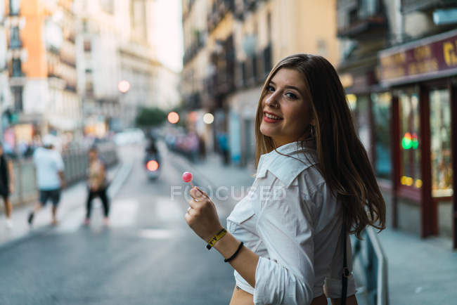 Брюнетка женщина с леденец, глядя через плечо на камеру — стоковое фото