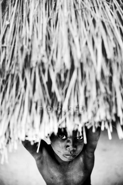 Гори, Сенегал - 6 декабря 2017 г.: Портрет черного ребенка, смотрящего из бунгало на камеру — стоковое фото