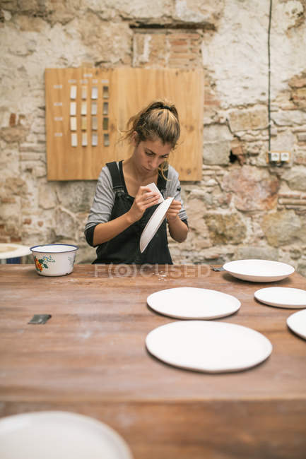 Front view of woman in apron sitting at table and forming plates from white clay. — Stock Photo