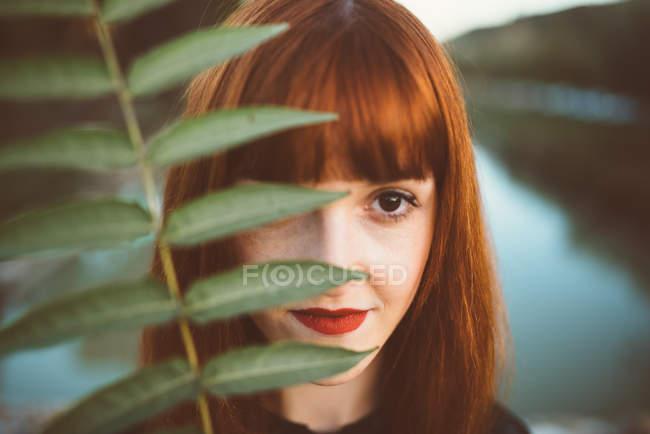 Рыжеволосая женщина с зелеными листьями — стоковое фото