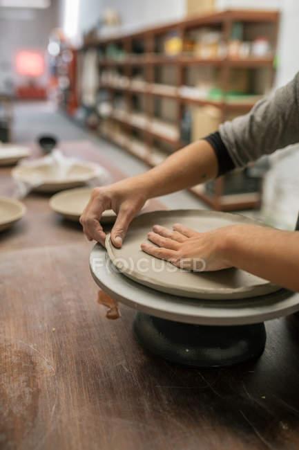 Обрезать женские руки, работая с глиной на рабочем столе — стоковое фото