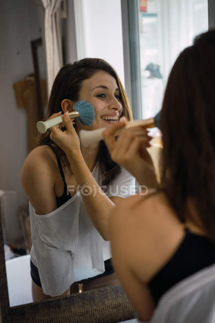 Jeune fille brune souriante debout près de miroir et l'application de rouge. — Photo de stock