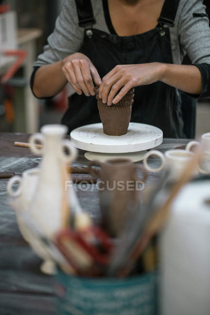 Mid section of woman forming pot from clay — Stock Photo