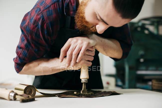 Bearded professional craftsman embossing gold ornament on piece of leather. — Stock Photo