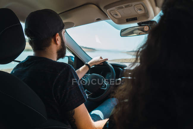 Vista posterior del hombre conduce el coche con pasajeros n - foto de stock