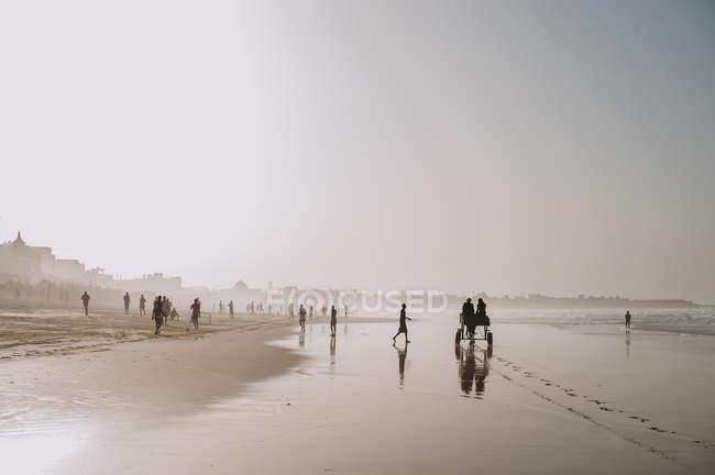 Yoff, Сенегалу - 6 грудня 2017: краєвид тропічного берегової лінії з піщаним пляжем і люди, що йдуть в серпанок світла. — стокове фото