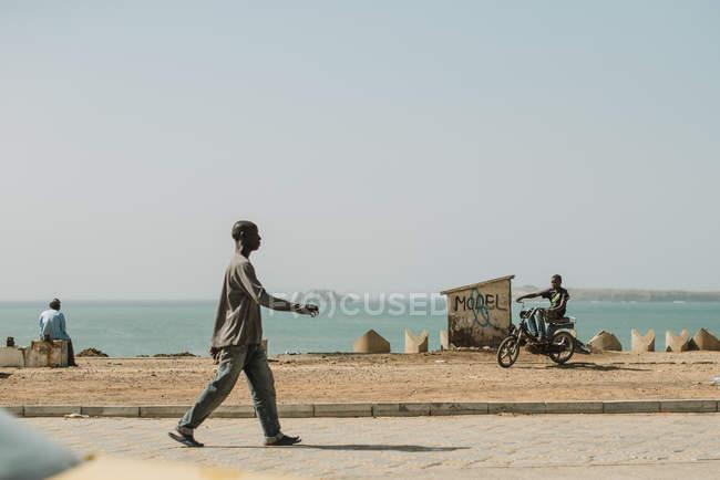 Goree, Senegal- December 6, 2017:Black people spending time on coastline of ocean in poor city. — Stock Photo
