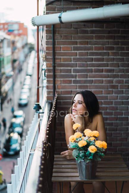 Брюнетка дівчина сидить за столом з кімнатні квіти на балконі і дивитися вбік — стокове фото