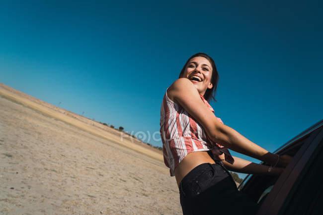 Ritratto di ragazza di risata appendere fuori equitazione finestra di automobile — Foto stock