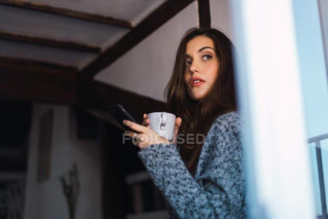 Брюнетка дівчина з чашкою кави і смартфон в руках, що хтось дивитися вбік — стокове фото