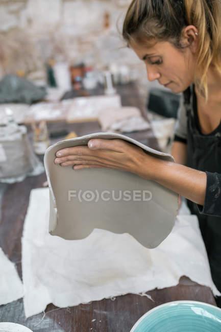 Вид сбоку блондинки, работающей с когтями в мастерской — стоковое фото