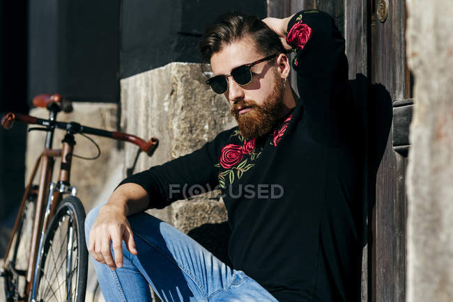 Portrait of man in sunglasses sitting near bicycle on street and posing at camera — Stock Photo