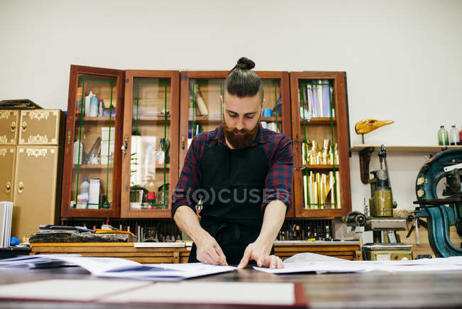 Young bearded man concentrated on work with papers in contemporary workshop of printing. — Stock Photo