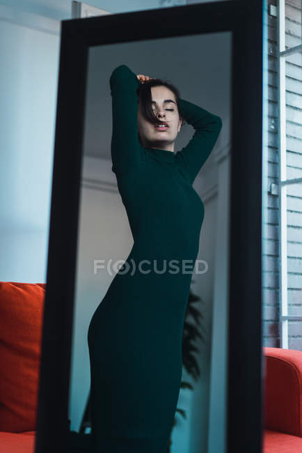 Portrait sensual brunette in green dress standing in front of mirror and posing with arms raised and eyes closed. — Stock Photo