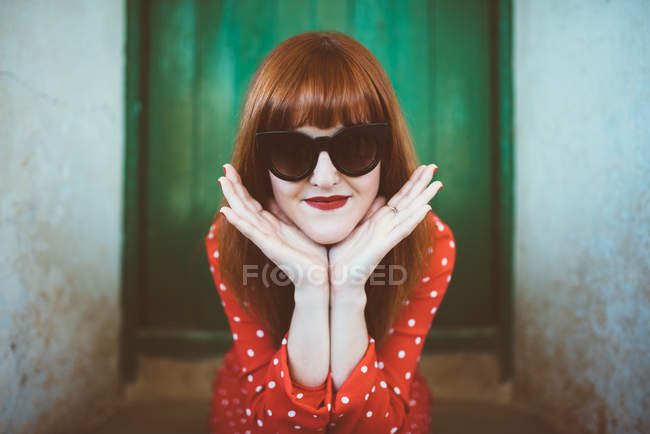 Portrait of redhead woman in red clothing and sunglasses posing with chin on hands — Stock Photo