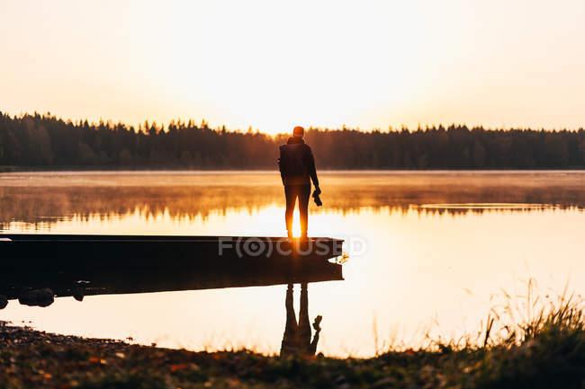 Silhouette eines Mannes mit Kamera in der Hand, der bei Sonnenaufgang auf dem See auf einem Boot posiert — Stockfoto