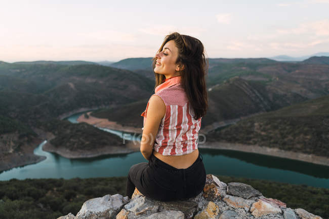 Stylish woman sitting on boulders and admiring mountain valley landscape — Stock Photo