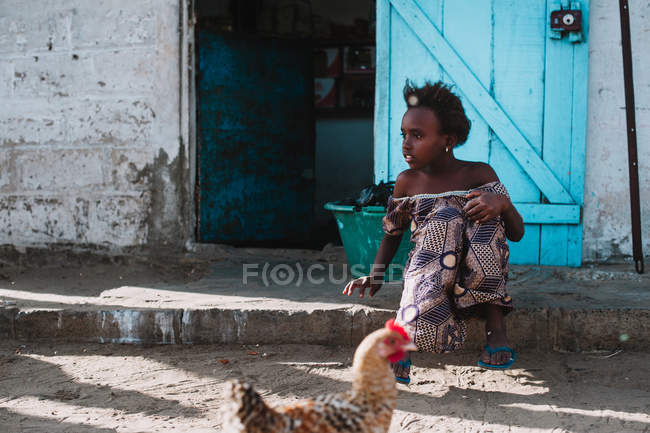 Yoff, Sénégal- 6 décembre 2017 : Jeune fille pauvre assise sur le seuil d'une maison dans un village . — Photo de stock
