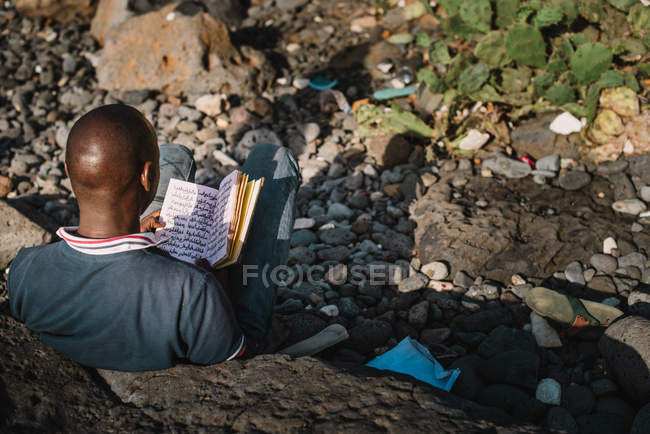 Over head view of African man reading book while sitting on rocks of shoreline. — Stock Photo