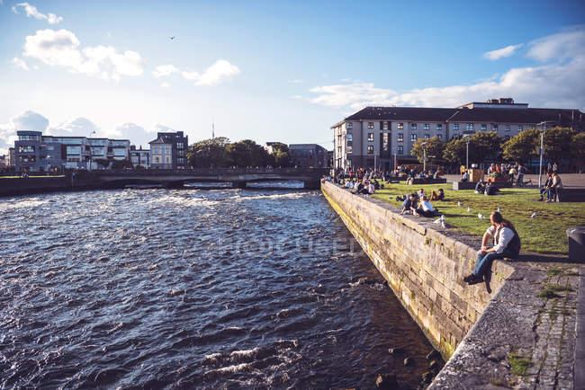 GALWAY, IRLANDE - 9 AOÛT 2017 : Les gens ont le temps sur les pelouses ensoleillées près du canal — Photo de stock