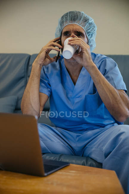 Portrait of doctor drinking coffee and talki — Stock Photo