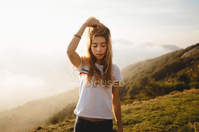 Junge Frau, die Haare am Hügel zu berühren — Stockfoto