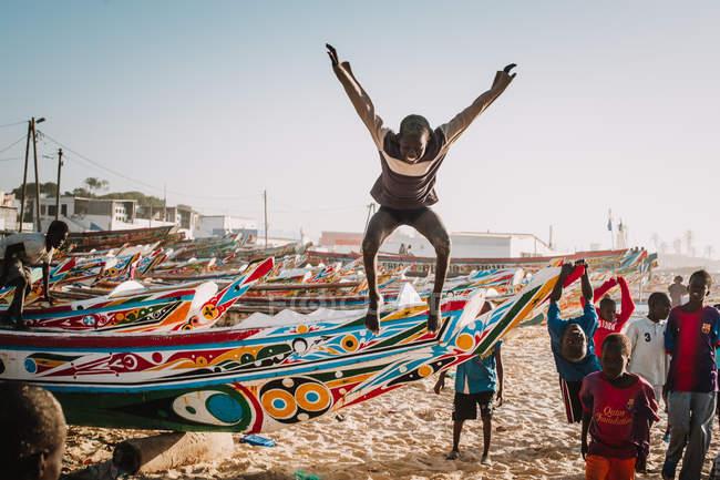 Yoff, Sénégal - 6 décembre 2017: groupe d'enfants africains s'amuser sur le rivage et sautant de peint lumineux voiliers — Photo de stock
