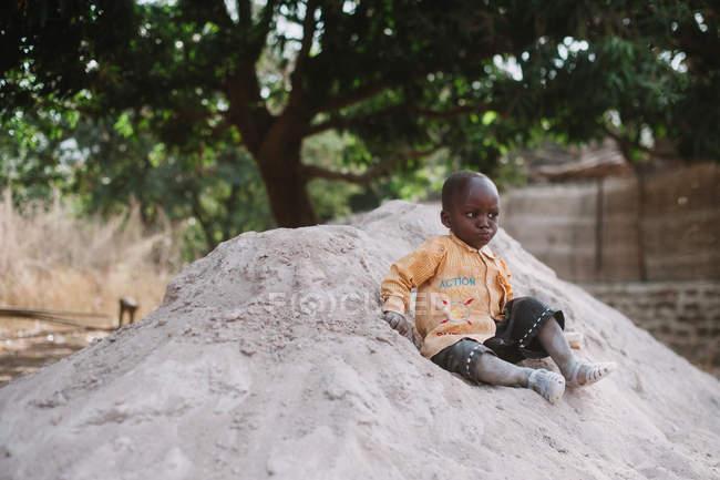 Kedougou, Сенегалу - 6 грудня, 2017:Portrait маленька дитина сидить на купі піску в сільській місцевості і серйозно дивлячись. — стокове фото