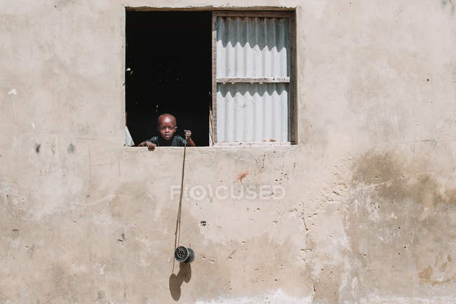 Goree, Sénégal- 6 décembre 2017 : Petit Africain regardant par la fenêtre et tenant une bobine — Photo de stock