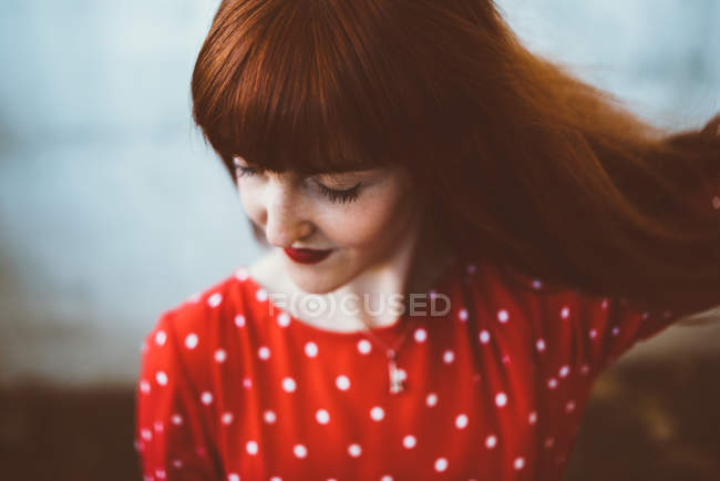 Redhead woman in red clothing and sunglasses waving hair andlooking down — Stock Photo