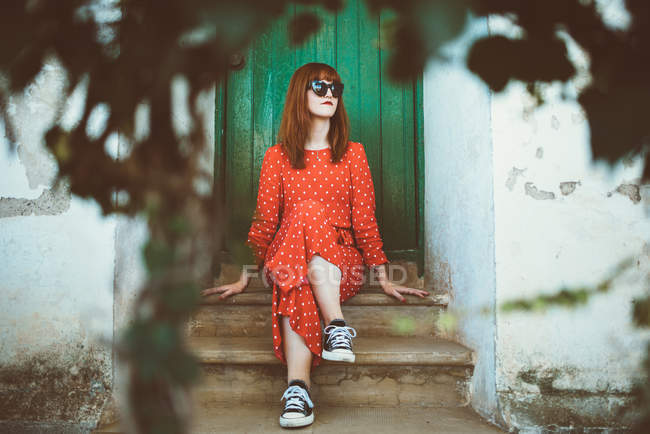 Redhead girl in sunglasses sitting on doorstep and looking away — Stock Photo