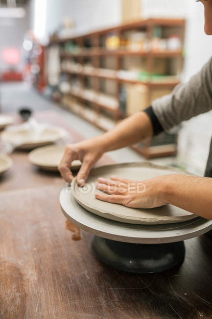 Crop potter working with clay at desktop in workshop — Stock Photo