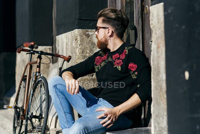 Ritratto di uomo con gli occhiali da sole seduto vicino alla bicicletta in strada e distogliendo lo sguardo — Foto stock