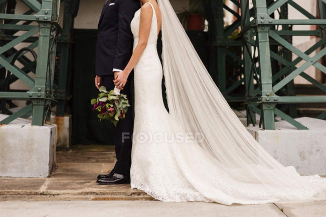 Mariée en robe de mariée et le marié avec fleurs posant ensemble récolte — Photo de stock