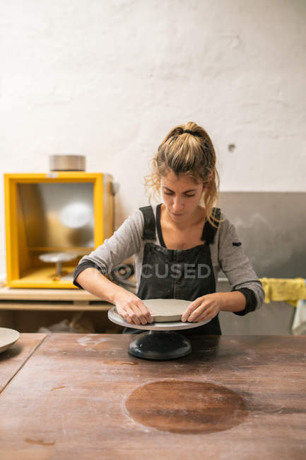 Front view of female potter carefully working with clay on table at workshop — Stock Photo