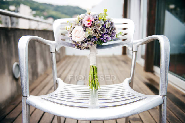 Beautiful bouquet placed on chair at terace — Stock Photo