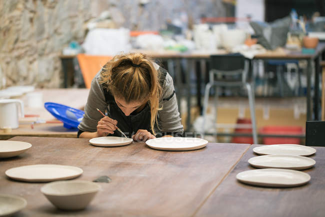 Bending woman creating clay plates in workshop — Stock Photo