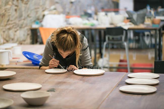 Согнутая женщина создает глиняные плиты в мастерской — стоковое фото