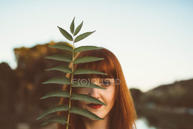 Portrait of ginger woman with red lips posing playfully and covering eye with leaves — Stock Photo