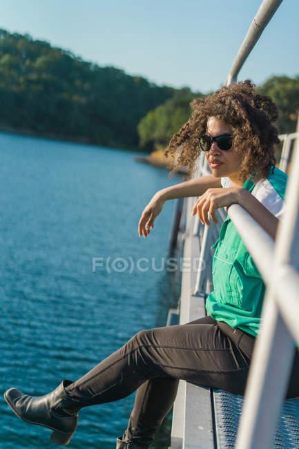 Porträt der Frau in Sonnenbrillen sitzen auf Pier über dem Wasser — Stockfoto