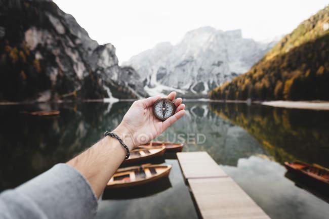 Bussola della holding da colture su sfondo di montagne e Lago — Foto stock