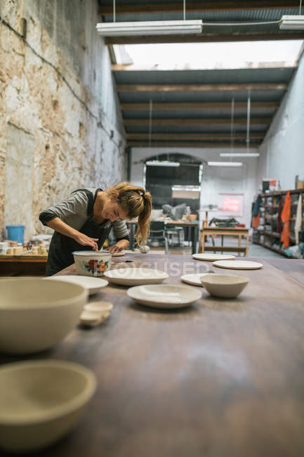 Side view of potter creating plates from white clay on table at workshop — Stock Photo